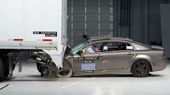 A car crashes into the back of a Stoughton trailer in a test of its underride guard conducted during the roundtable